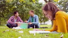 Student writing notes with males using laptop at park - stock photo