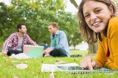 Student using tablet PC while males using laptop in park - stock photo