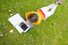 Female student using tablet PC in the lawn - stock photo