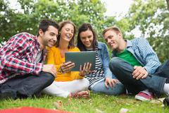 College students using tablet PC in park Stock Photos