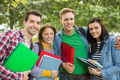 Stock Photo of Portrait of college students with bags and books in park