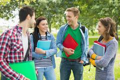 Cheerful young college students in park Stock Photos