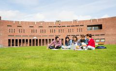 Students using laptop in lawn against college building Stock Photos