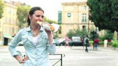 Happy young woman eating baguette by the city street HD Stock Footage