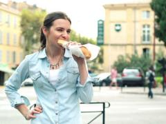Happy young woman eating baguette by the city street NTSC Stock Footage