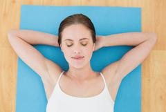 Stock Photo of Woman resting on exercise mat with eyes closed