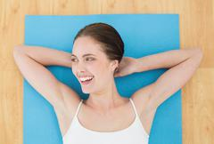 Stock Photo of Cheerful woman lying on exercise mat