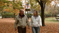 Middle Aged Couple Walking In A Park  During Fall Autumn Weather - stock footage