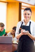 Waitress writing an order with students using laptop at  coffee shop - stock photo
