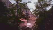 Stock Video Footage of Montserrat monastery behind trees  cloudy sky