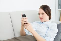 Smartly dressed woman reading text message while lying on sofa Stock Photos