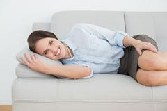 Smiling well dressed woman relaxing on sofa Stock Photos