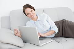 Stock Photo of Portrait of a smiling well dressed woman using laptop on sofa