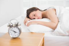Woman in bed with alarm clock on bedside table - stock photo