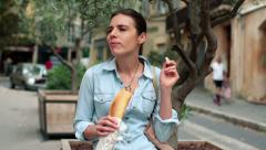 Young woman eating baguette in the city HD Stock Footage