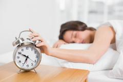 Sleepy blurred woman in bed extending hand to alarm clock - stock photo