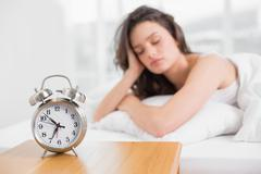 Sleepy woman with alarm clock in foreground - stock photo