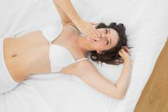 Beautiful woman in lingerie yawning on bed Stock Photos