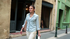 Happy woman walking on street having baguette in slow motion HD Stock Footage