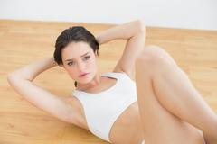 Sporty fit woman doing sit ups in fitness studio - stock photo