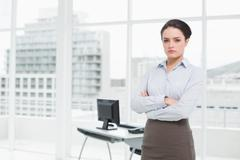Elegant businesswoman standing with arms crossed in office - stock photo