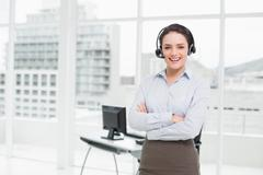 Smiling elegant businesswoman wearing headset with arms crossed in office - stock photo