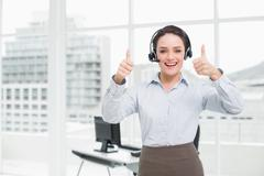 Elegant businesswoman wearing headset while gesturing thumbs up in office Stock Photos