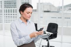 Serious businesswoman reading text message in office - stock photo