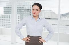 Elegant businesswoman standing with hands on hips in office Stock Photos