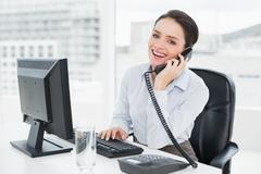 Smiling businesswoman using landline phone and computer in office - stock photo