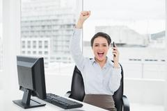 Elegant and happy businesswoman using cellphone in office Stock Photos