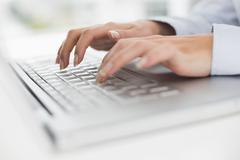 Stock Photo of Close up of hands typing on laptop keyboard