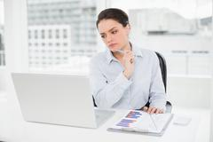 Businesswoman with graphs and laptop in office - stock photo