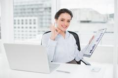 Stock Photo of Businesswoman with graphs and laptop gesturing okay sign in office