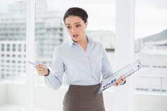 Elegant businesswoman with graphs in office - stock photo