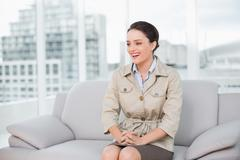 Cheerful well dressed woman sitting on sofa at home - stock photo