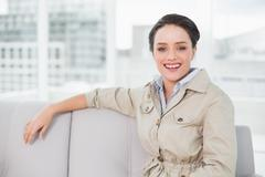Stock Photo of Smiling well dressed young woman sitting on sofa