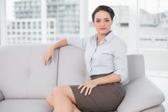 Serious well dressed young woman sitting on sofa at home - stock photo