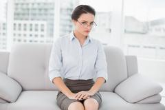 Serious well dressed woman sitting on sofa - stock photo