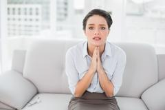 Worried well dressed woman with joined hands at home - stock photo