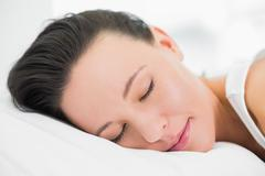 Stock Photo of Pretty young woman sleeping in bed