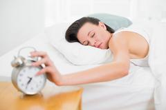Woman in bed with eyes closed extending hand to alarm clock - stock photo
