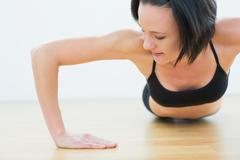 Determined woman doing push ups in fitness studio - stock photo