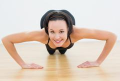 Stock Photo of Smiling beautiful woman doing push ups in fitness studio