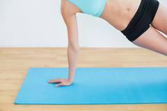 Slim woman doing the side plank yoga pose - stock photo