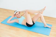 Sporty fit woman doing sit ups on exercise mat - stock photo