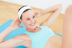 Smiling woman doing sit ups on exercise mat Stock Photos