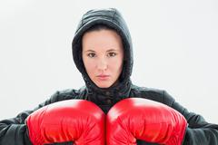Beautiful young woman in hood and red boxing gloves Stock Photos