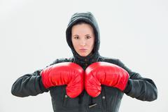 Beautiful woman in hood and red boxing gloves - stock photo