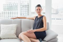 Serious well dressed woman sitting on sofa at home - stock photo